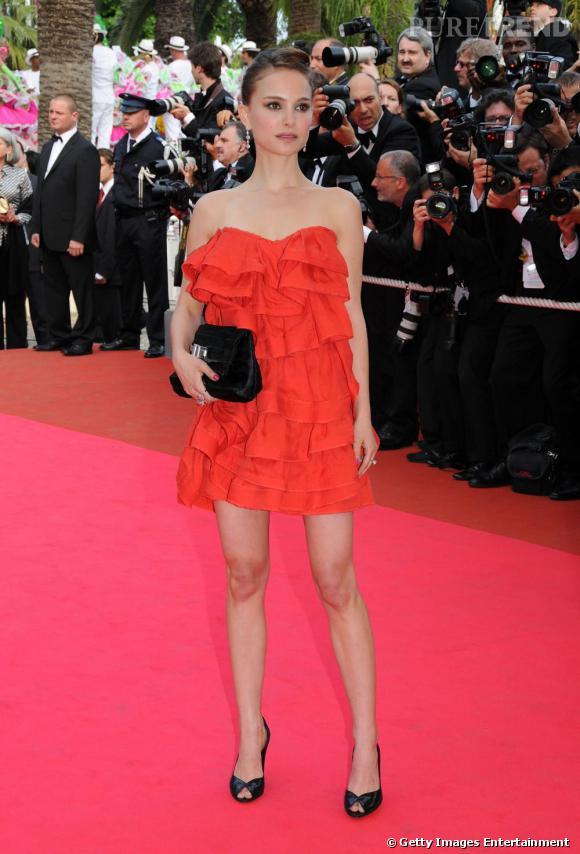 Natalie Portman tente la robe à froufrous et mise sur une accessoirisation plus sobre avec une pochette noire.