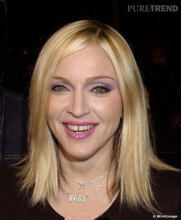 Pour le nouveau millénaire Madonna revient au blond avec une coupe effilé et des mèches caramel. Accroc au make-up girly, elle choisit un gloss rose bonbon.