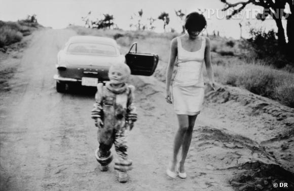 PETER LINDBERGH : DÉCRYPTAGE D'UN STYLE EN 5 IMAGES                  N'allez pas croire que le maître allemand manque d'humour. Au contraire, Peter Lindbergh aime pimenter ses photos d'une certaine bizarrerie, faisant souvent référence aux films de science-fiction des années 50. En 1990, il photographie Helena Christensen en Californie pour le Vogue italien, accompagnée d'une étrange créature difficile à identifier. Serait-ce un cosmonaute égaré ramenant Helena sur terre ou un martien en détresse? Lindbergh ouvre les portes du narratif, imaginant un scénario multiple digne de David Lynch.