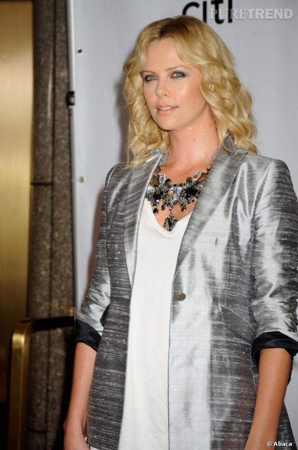 Charlize Theron se fait un look ultra brillant en veste argenté et collier Dior.