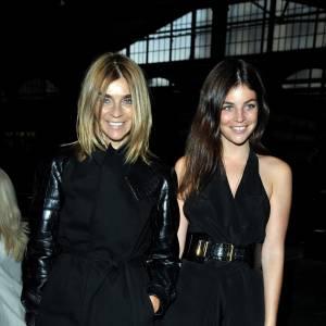 Carine et Julia Restoin Roitfeld optent pour un total look black. Si la  mère porte une paire de bottes et une jupe mi-longue, la fille s'est  parée d'une robe courte et d'escarpins à plateforme. Elles assument  chacune parfaitement le style qui convient à leur âge.