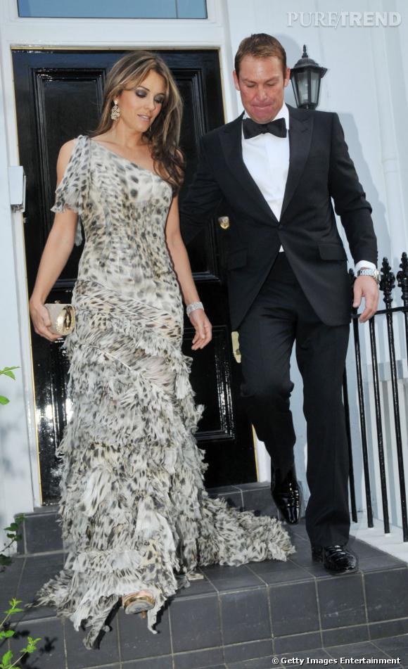 Elisabeth Hurley, en longue robe asymétrique et ornée de froufrous, accompagnée de son nouvel homme, Shane Warne.