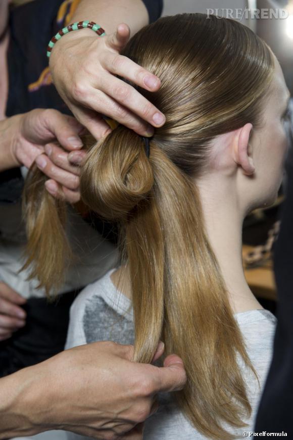Chignon plat : mode d'emploi     Etape   3 : la consolidation.    Maintenir la boucle entre vos mains, travailler l'autre mêche pour  qu'elle enroule ce chignon. Cette mèche de cheveux doit masquer  l'élastique de la pony tail.