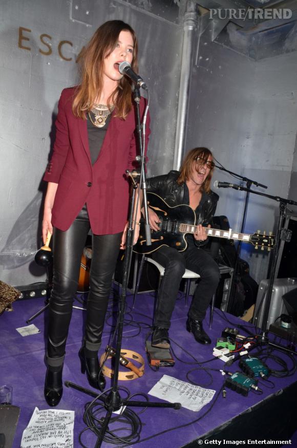 Sur scène, Lou en impose avec son ensemble pantalon en cuir et blazer bordeaux élégant.