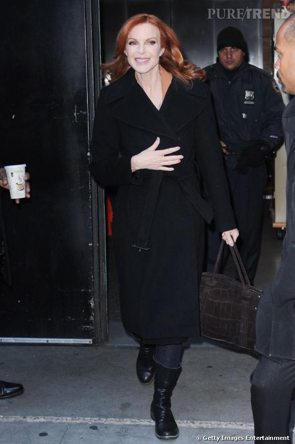 L'actrice porte un manteau noir ceinturé à la taille très élégant.