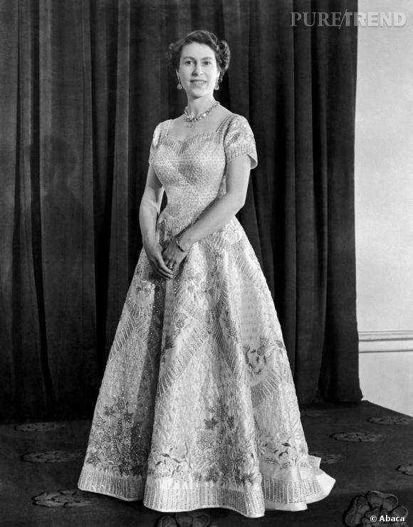 Le jour de son couronnement elle mise sur une longue robe brodée par le couturier Norman Hartnell.