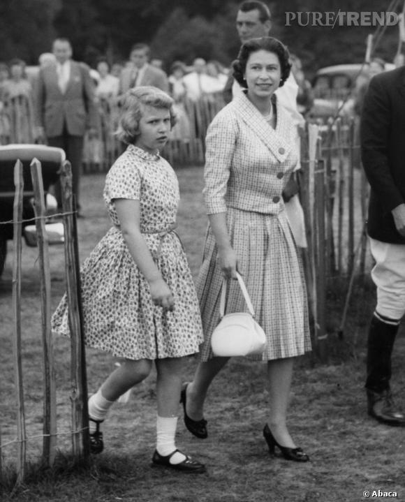 Toujours chic, même pour assister à un match de polo, la Reine suit la tendance 60's avec une jupe midi et un sac madame.