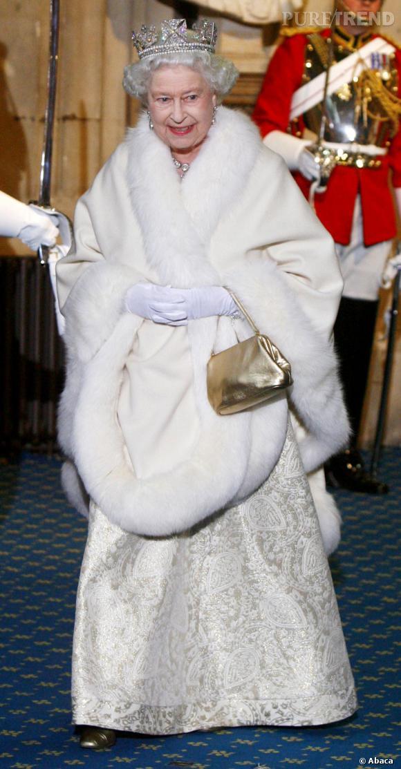 Robe immaculée brodée, cape en fourrure et mini sac doré, la Queen est toujours chic et féminine.