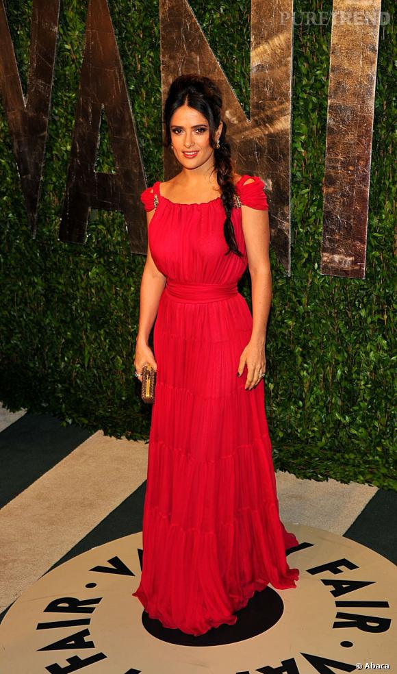 Salma Hayek porte une robe rouge Yves Saint Laurent au drapé théâtral.