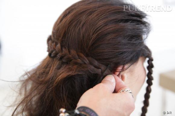 On passe une tresse par l'arrière de manière à ce qu'elle fasse le tour de la tête et qu'elle arrive au niveau de l'oreille opposée. On la fixe avec la pince plate utilisée pour la maintenir.