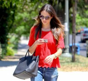 Slippers aux pieds, elle enfile un jean et un top en crochet rouge.