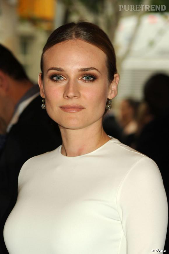 Diane Kruger opte pour une robe blanche et réchauffe son maquillage avec des fards cuivrés et dorés.