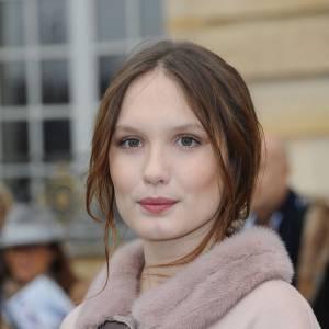Un brin rétro dans son manteau pastel, la Française se coiffe d'un chignon flou.