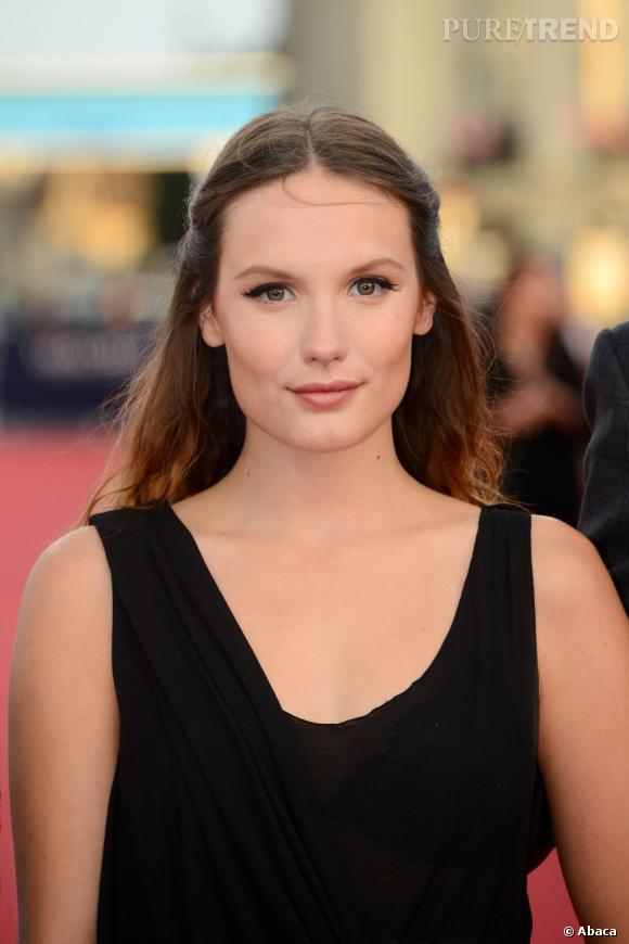 """Style romantique pour l'actrice de la série """"Les Revenants"""". Elle se coiffe d'une demi-queue bardée d'une raie au milieu."""