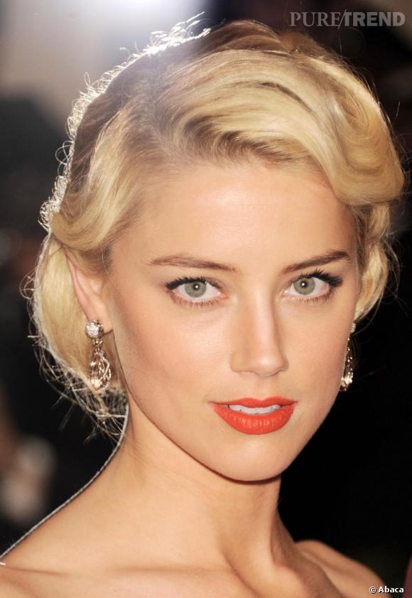 Sublimée par un chignon rétro, Amber Heard mixe bouche carmin et eyeliner pour un maquillage de pin up chic.