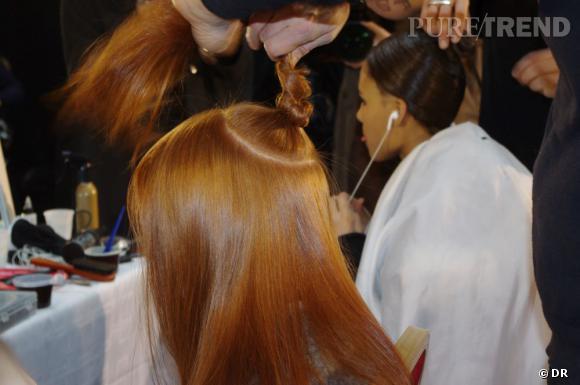 Les cheveux au centre du crâne sont isolés en un chignon le temps de créer le look wet. Ils seront ensuite lissés à la perfection.