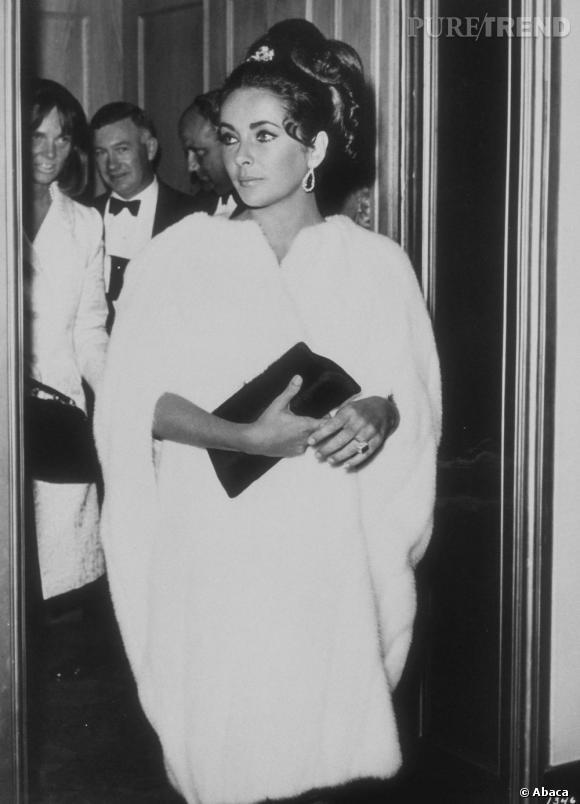 Elizabeth Taylor, en long manteau de fourrure effet cape blanche, à la fois élégante et sophistiquée.