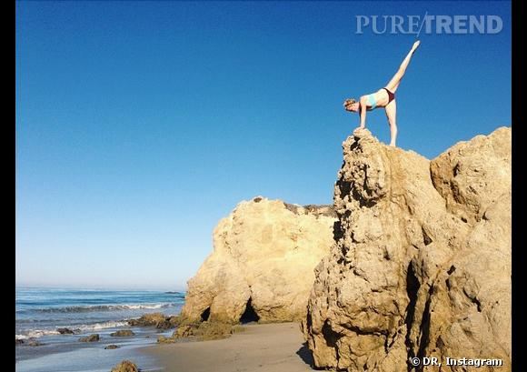 Ireland Baldwin fait du yoga... sur la plage.