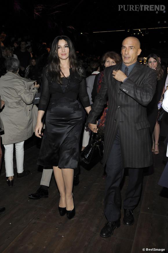 Monica Bellucci arrive au défilé Dolce & Gabbana Automne-Hiver 2015. Elle tient son garde du corps par la main.