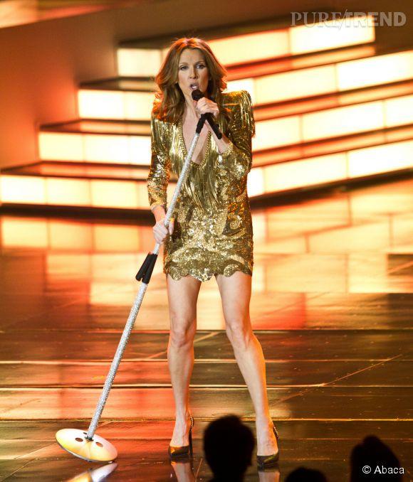 Céline Dion en robe à sequins dorés, décolleté plongeant et épaules structurées qui dévoile ses longues et fines jambes.