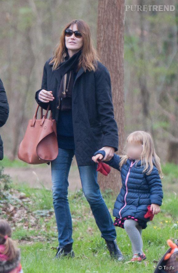 """Carla Bruni-Sarkozy en ballade dans le parc de Saint-Cloud avec sa petite Giulia. Au bras, le sublime """"Cape Bag"""" de Tod's."""