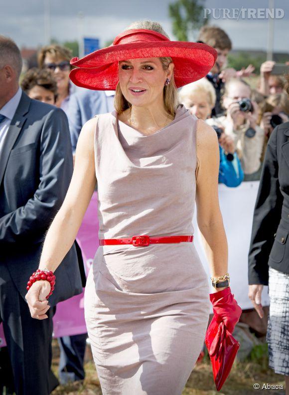 Trouvant sa robe beige peut être un peu trop terne à son goût, la reine fait fort côté accessoirisation.