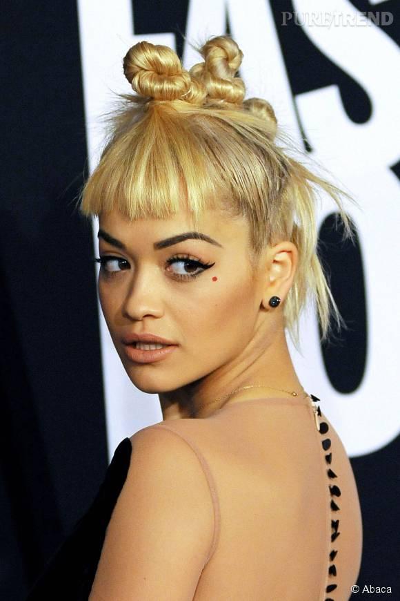 Frange un peu courte, mini chignons sur le dessus, on ne voit pas l'intérêt de la coiffure de Rita Ora.