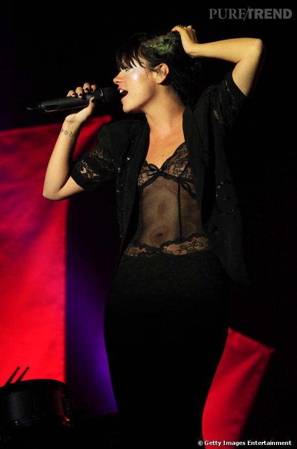Pour un look sexy, Lily Allen puise sa tenue de scène dans l'univers de la lingerie, avec un body transparent de dentelles noires. Associé à un boléro rebrodé de sequins et un pantalon noire: il en devient chic. Une plume de paon dans les cheveux: Lily est au top.