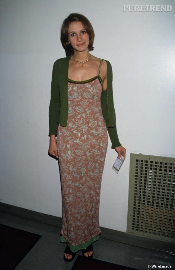 Longue robe à fleurs, la rouquine flatte sa plastique menue mais pas son teint. Le gilet vert n'est pas du meilleur goût.
