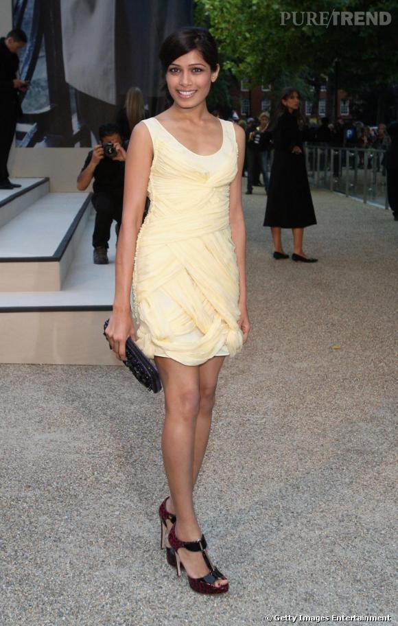 En robe jaune pastel Burberry, la peau mate de Freida est sublimée.