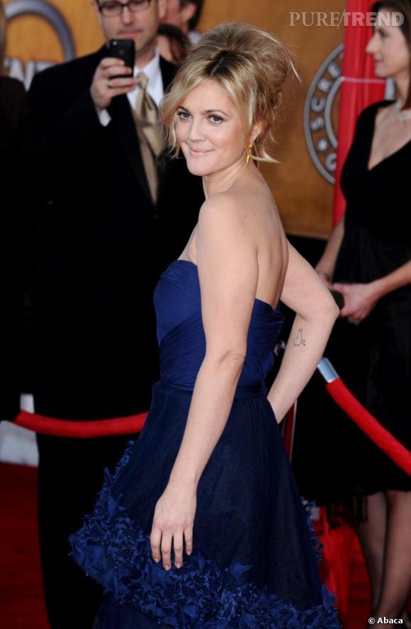 Drew Barrymore fait partie des filles les plus décalées. Certainement fan de  30 Millions d'Amis , elle opte pour un poussin juste sous le coude.