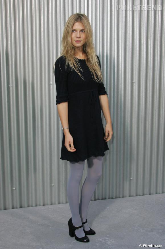 Clémence délaisse le look rock pour une tendance plus preppy en petite robe noire. Associée à un collant gris et une paire de babies compensées, elle y ajoute une touche de modernité.