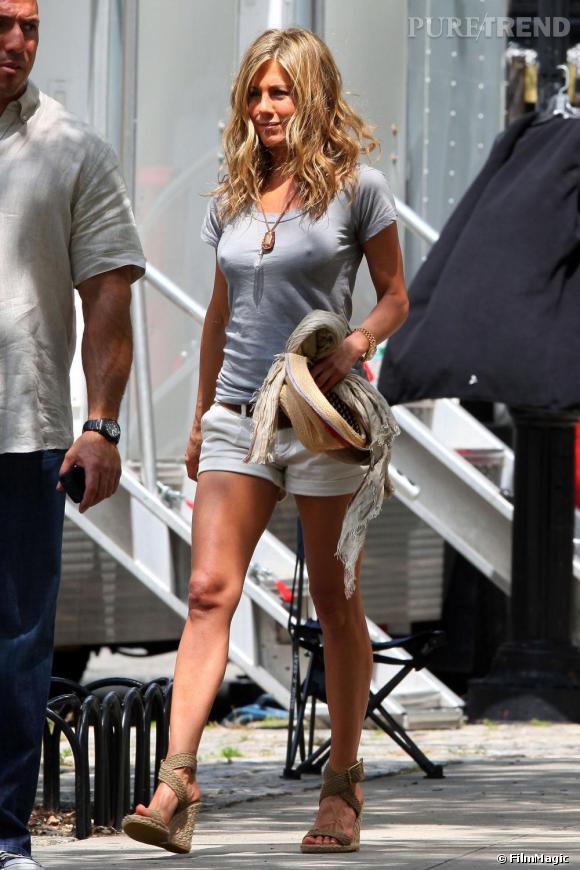 Jennifer Aniston opte pour le duo de charme, le chapeau de paille et les compensées Stuart Weizman avec un short court.