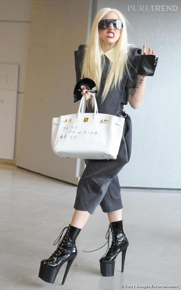 A l'aéroport de Narita, Lady Gaga ose le look gothico-fashion. Bottes à plateaux XXL, robe démesurée et sac Hermès, elle est de loin la reine du Mix'n match.