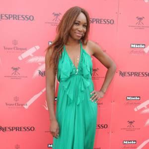 Venus Williams se fait une silhouette délicate, en robe vert jade, longue et très fluide. Les sandales dorées plates soulignent son allure très bohème.