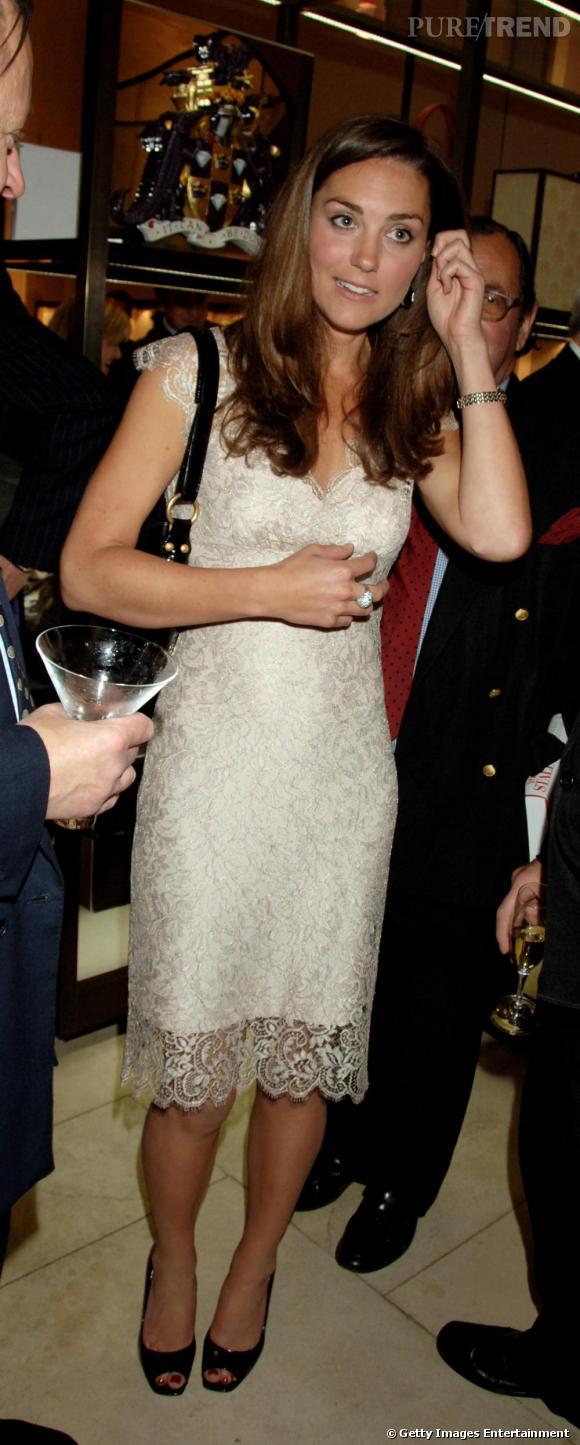 Le robe blanche :  Kate opte pour une petite robe très chic qui joue sur un jeu de dentelles. Sage, le vêtement s'arrête au niveau du genou.
