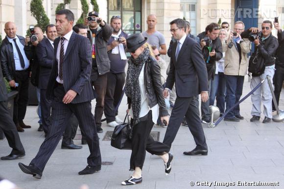 Madonna, entourée d'une horde de photographes à la sortie de son hôtel, à Paris.