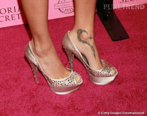 Elle essaie de nous éblouir avec ses chaussures dorées mais on remarque tout de même son tatouage au pied.