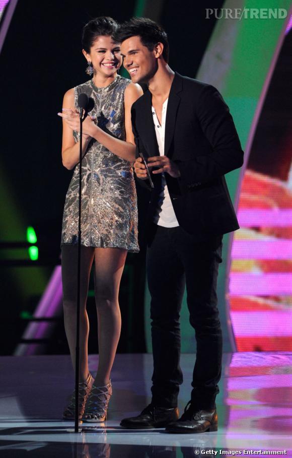 Sur scène aux côtés de Taylor Lautner, Selena opère un changement de tenue avec une mini-robe argentée.