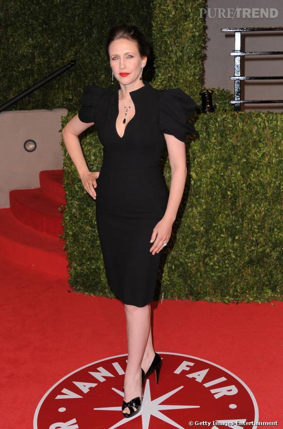 Crinière domptée de manière sophistiquée, lèvres ourlées d'un rouge profond et la silhouette flattée par une petite robe noire à la facture dramatique, l'actrice se complaît dans un style rétro et un brin vamp.