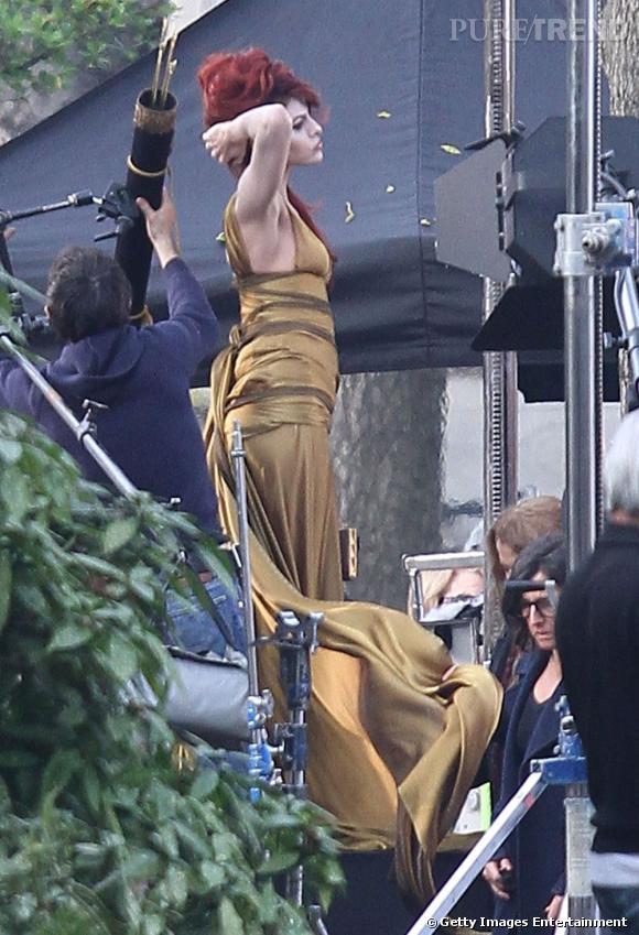 Eva Mendes dans une robe verte et or détient une crinière rouge.
