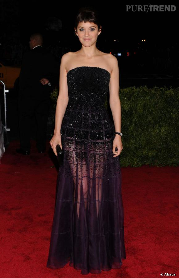 Marion Cotillard complète sa tenue avec une pochette Dior.