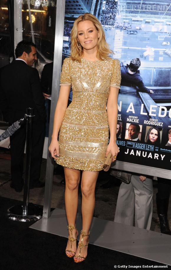 Elizabeth Banks rayonne dans une robe dorée parsemée de paillettes et sequins.