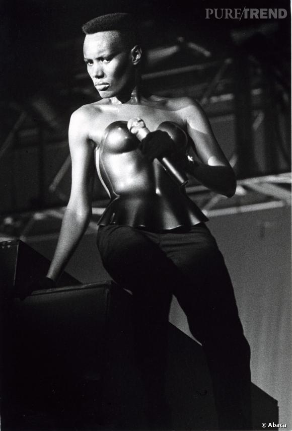 Grace Jones mixe coupe millitaire et bustier seconde peau. Un modèle du style.