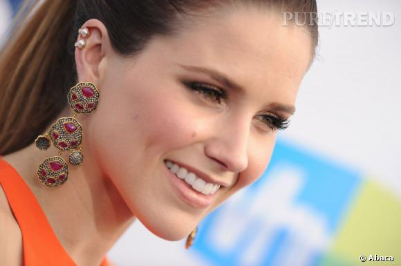 Elle complète son look par des boucles d'oreilles XXL et des perles sur le haut du cartilage