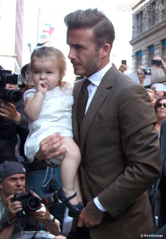Harper Beckham dans les bras de son père de footballeur vient voir le défilé de sa mère. C'est ça une baby fashionista.