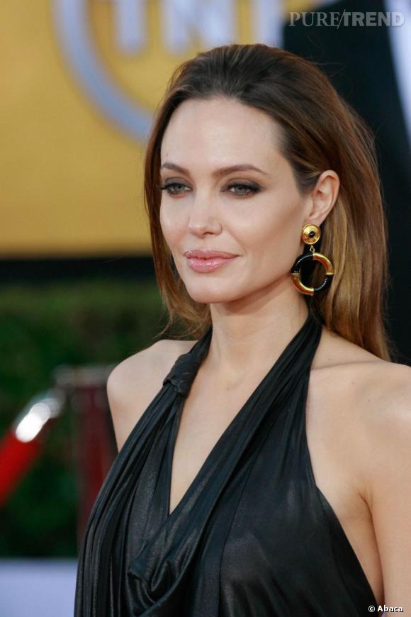 Angelina Jolie apporte une touche gold et noir en harmonie avec son make-up charbonneux.