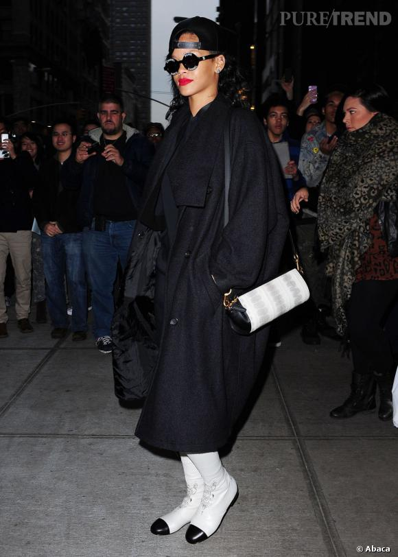 Rihanna se camoufle sous un long manteau noir et enfile d'étonnantes bottes blanches à bout noir.