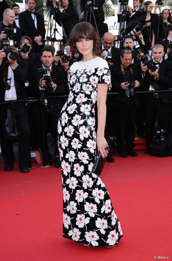 """Milla Jovovich en robe et pochette Chanel et des bijoux Swarovski à la montée des marches, pour la projection de """"Blood Ties""""."""
