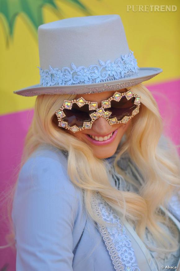 Kesha joue la carte de l'audace et associe haut de forme pastel et boucles platines.